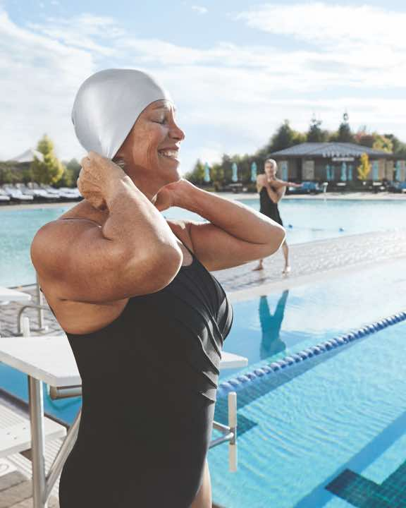 Woman wearing a swim cap standing next to an outdoor lap pool at Life Time