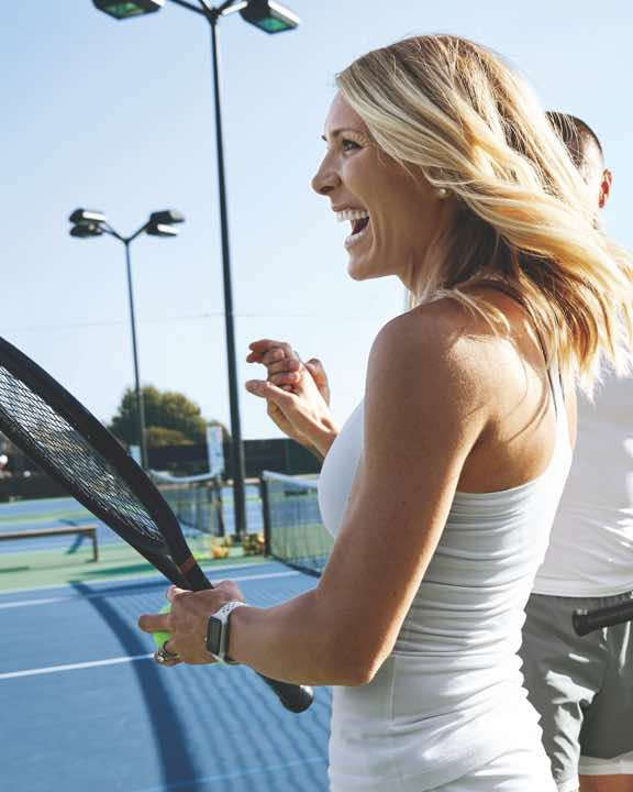 Smiling woman holding a tennis racquet on an outdoor tennis court at Life Time