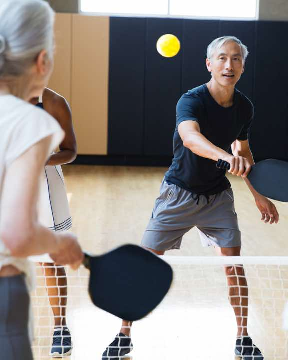 Group of people playing pickleball on an indoor pickleball court at Life Time