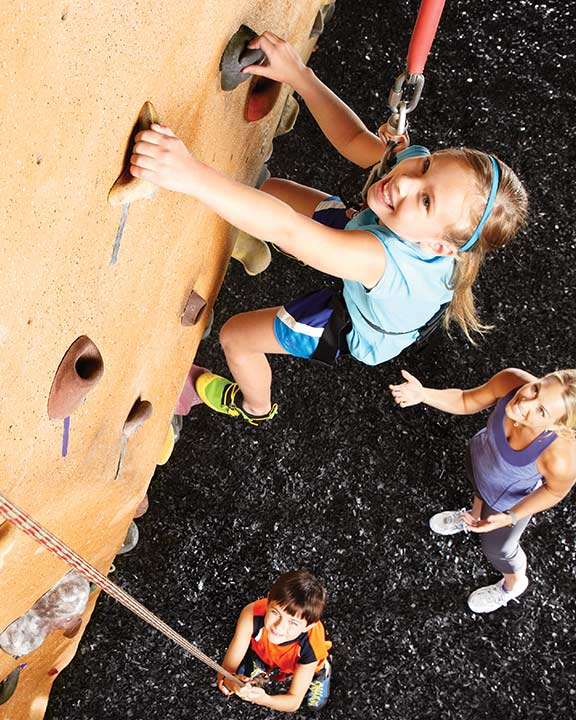 a yound girl climbs an indoor rock wall at life time while a woman and boy watch from below