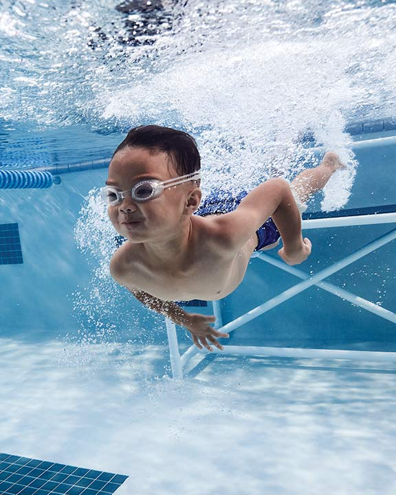 Little boy taking swimming lessons in a pool at Life Time