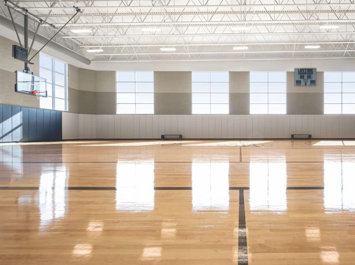 Indoor basketball court at Life Time with gleaming wood floors