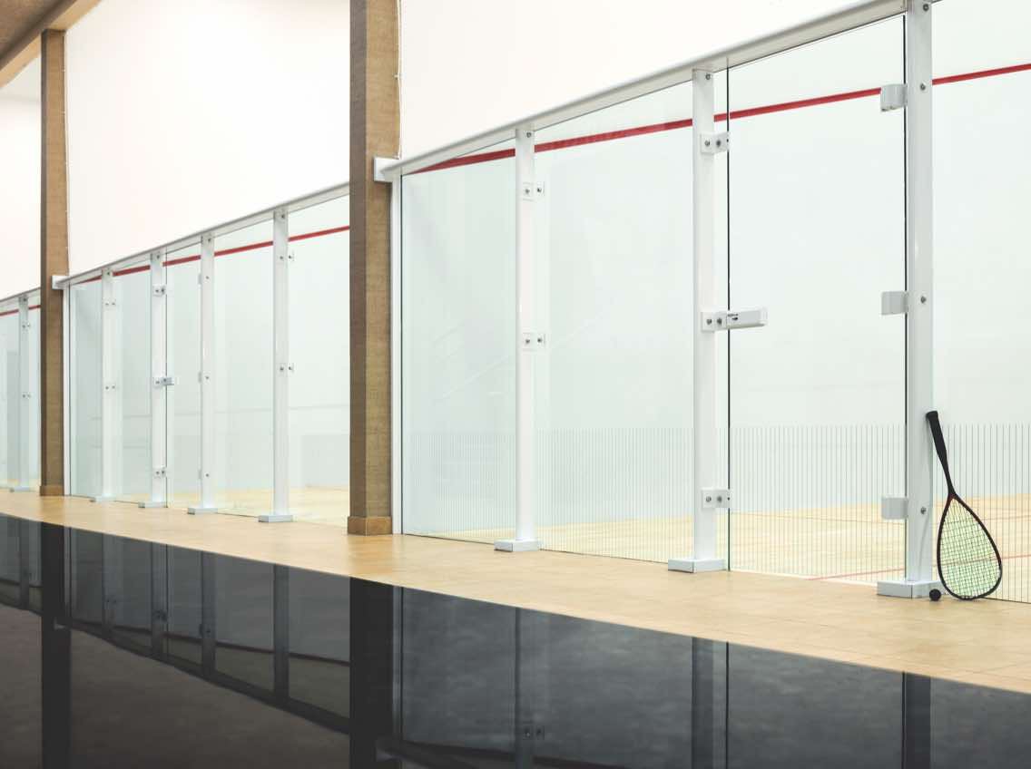 A row of four racquetball courts enclosed in glass windows at Life Time