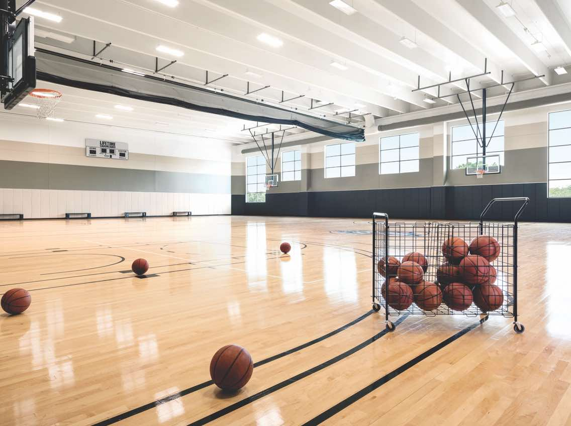 Large cage of basketballs on an indoor basketball court at Life Time