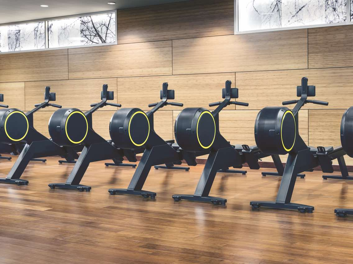 Row of rowing machines on a wooden floor at Life Time