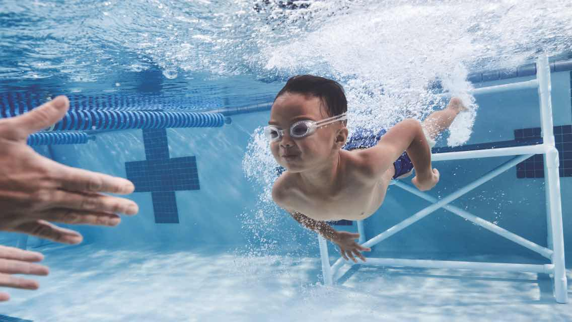 Little boy swimming underwater during swimming lessons at Life Time.