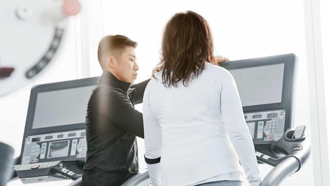 Personal trainer helping a female member on a treadmill during a personal training session.