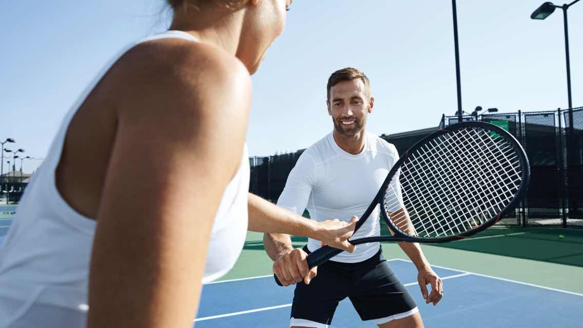 Man and woman taking tennis lessons at Life Time.