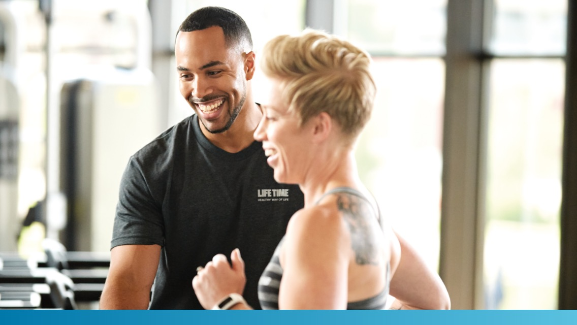 A male trainer helping a female member during a personal training session at Life Time.