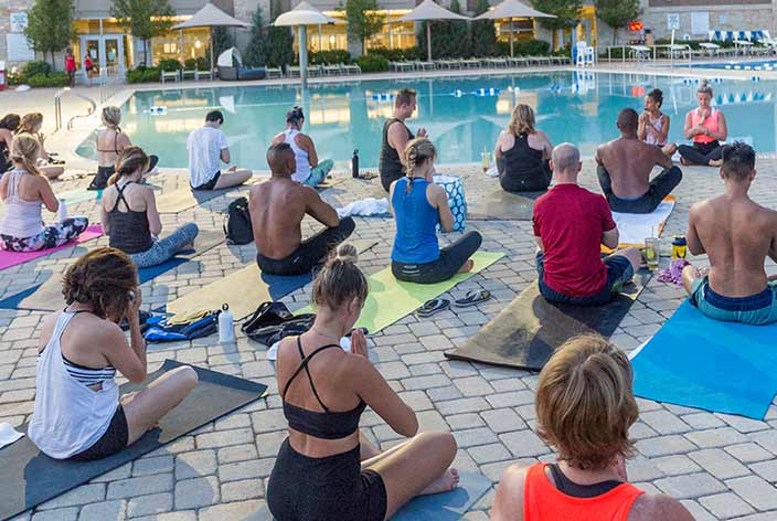 Club Events: Life Time members pose in a poolside yoga class