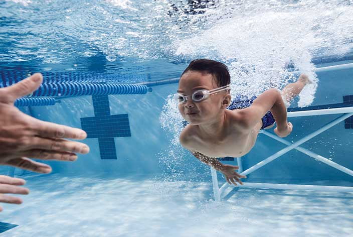 Kids Swim: A child in swim lessons at Life Time aquatics facilities