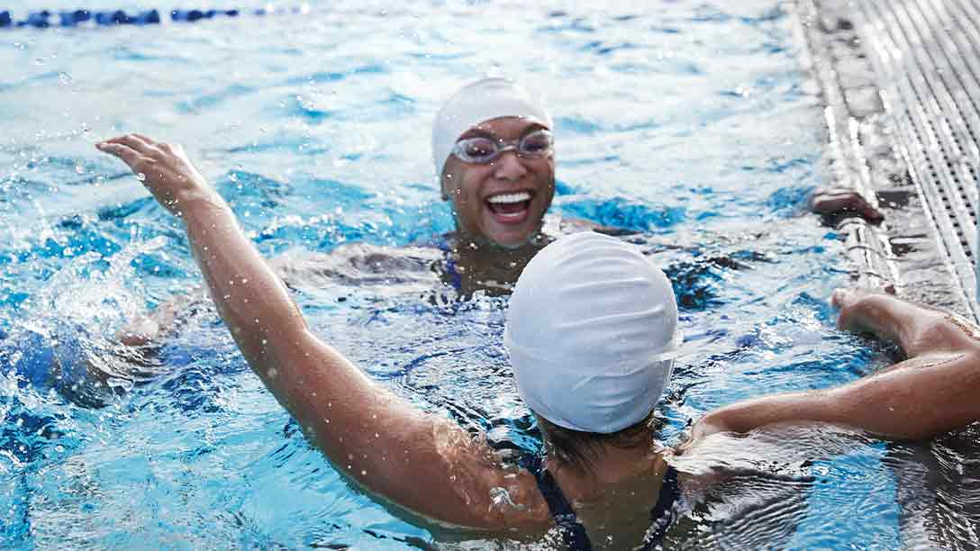 2 women smile and laugh while resting at the pool while during lap swim