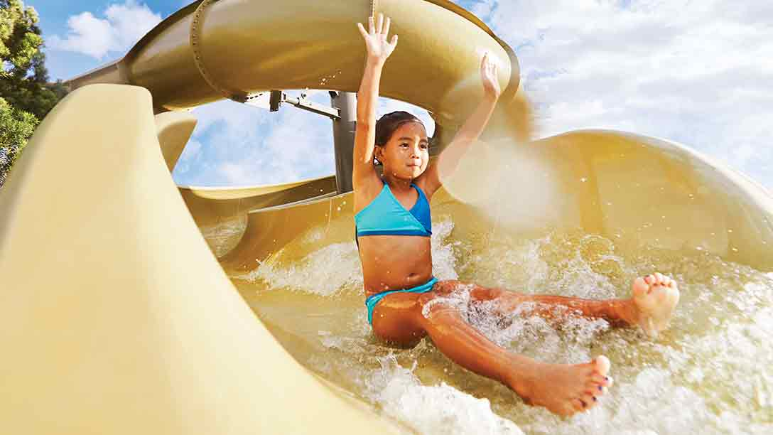 A child enjoying summer fun on the outdoor waterslide
