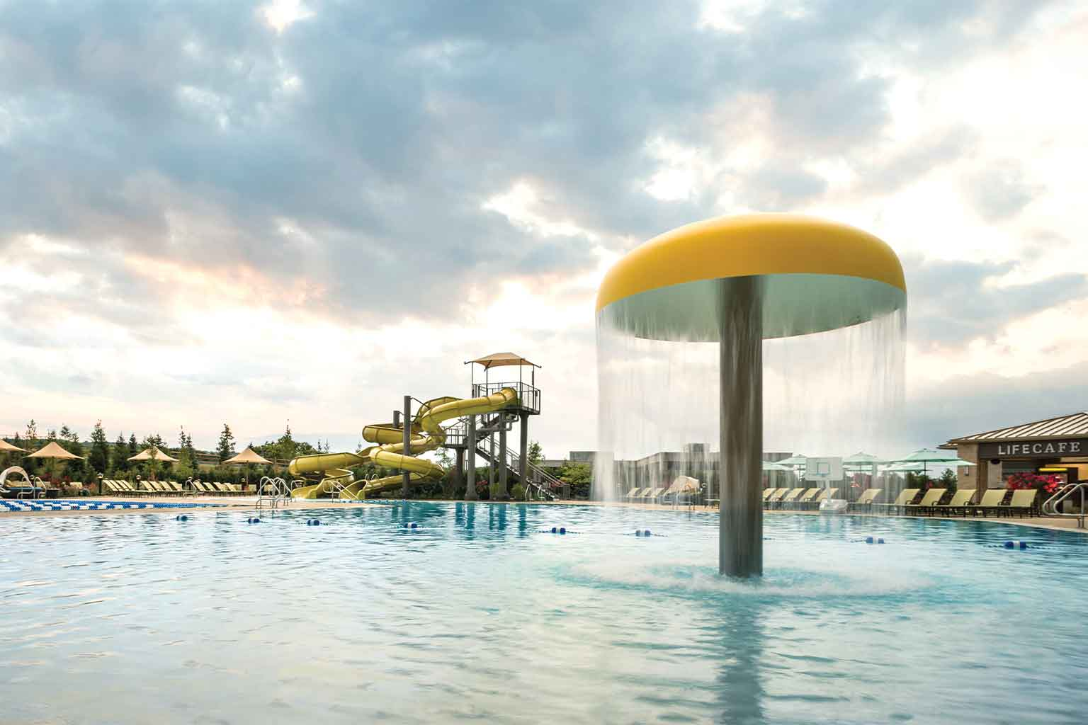 A yellow water feature and waterslides at a Life Time outdoor pool.