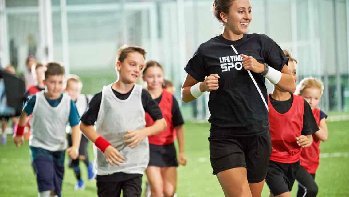 A Life Time Sport coach leads a group of kids wearing soccer jerseys on a jog on an indoor soccer field