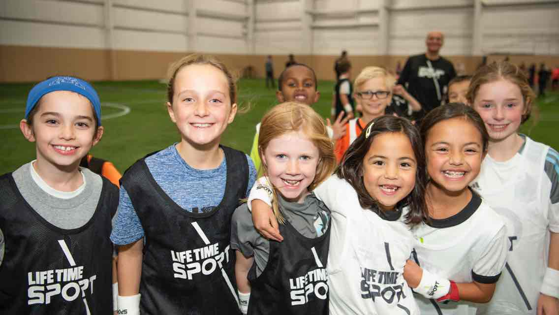 A group of children wearing Life Time Sport jerseys stand smiling with their arms around each other on an indoor soccer field