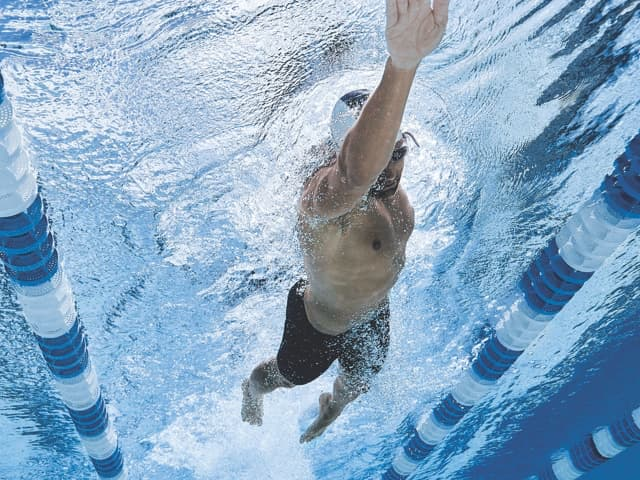 An underwater view of a male swimmer swimming laps at a Life Time pool