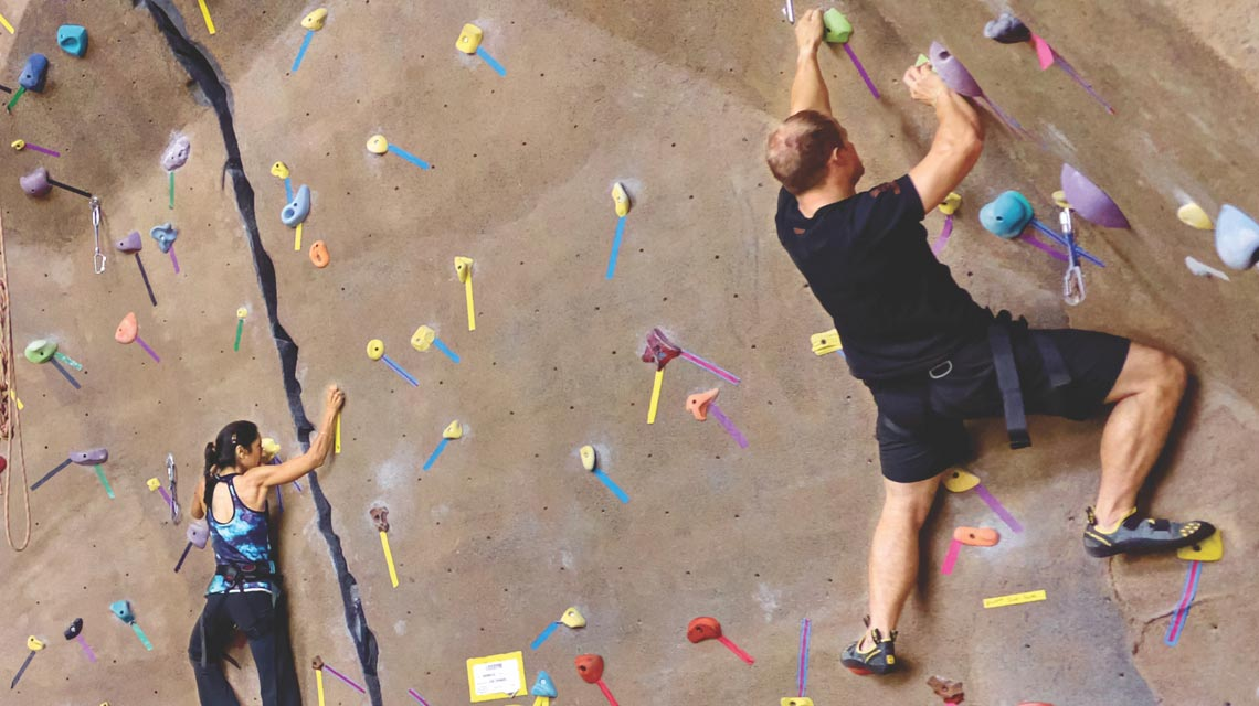 a man and a women scaling an indoor rockclimbing wall at a life time location