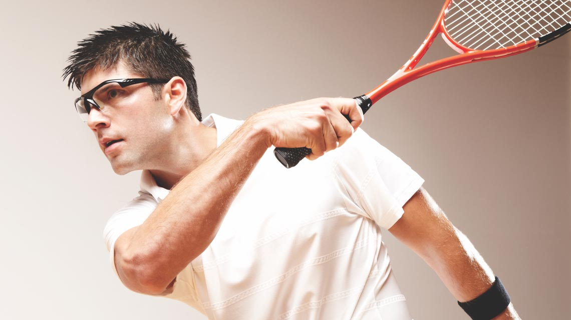 A man after swinging his squash racquet