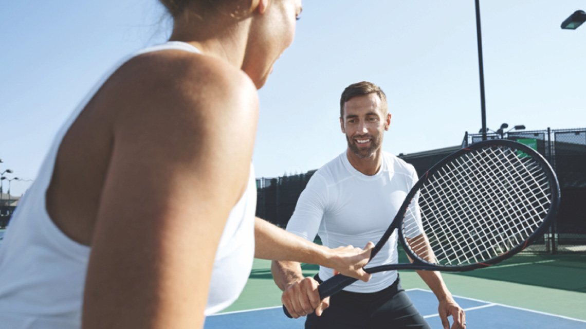 A man receives instruction on his racquet from a Life Time Tennis Instructor on an outdoor Life Time Tennis court