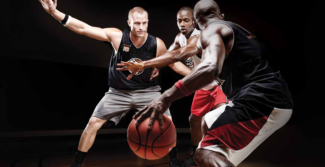 Three athletic men playing basketball together