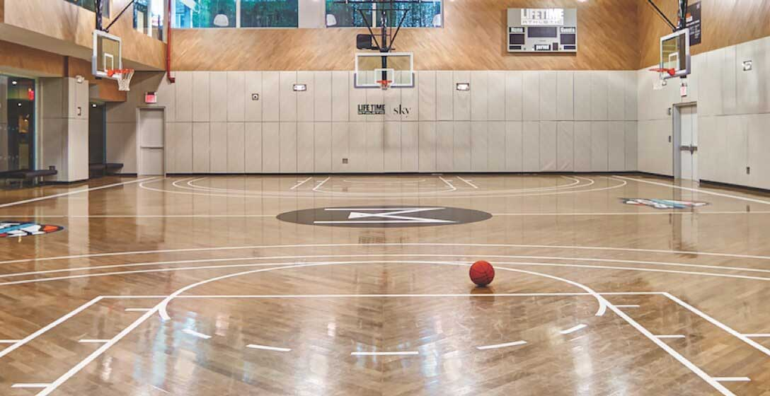 A basketball sitting near the center of a beautiful basketball court with shiny wood floors
