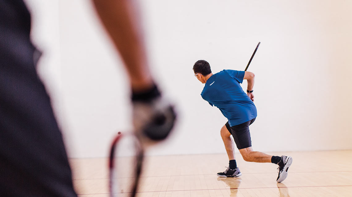 A man swings his racquet with his opponent in the foreground of the racquetball court