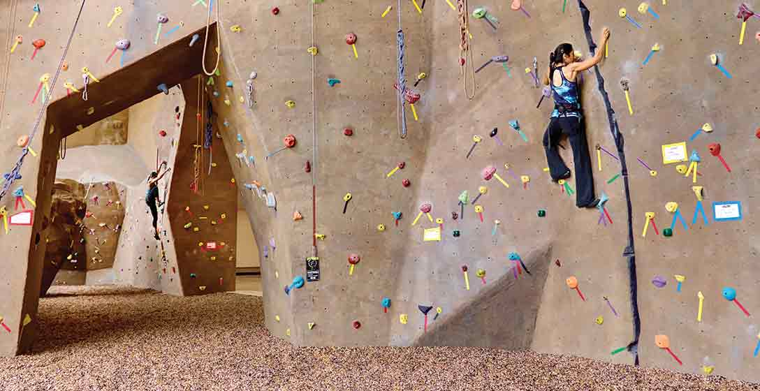 A coach watching two adults on an indoor climbing wall