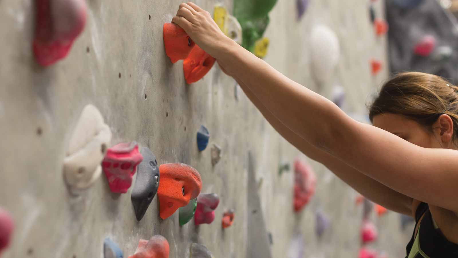 A woman reaching to grab a hold above her while bouldering