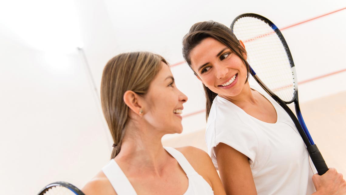Two women talking and holding squash racquets