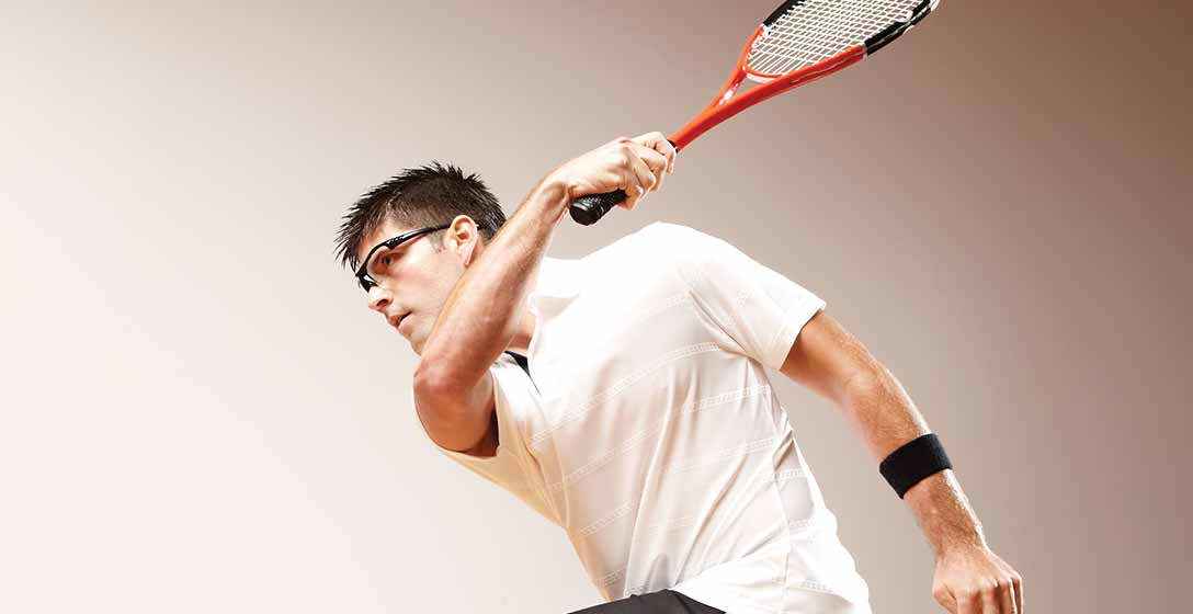 A man wearing squash athletic gear taking a swing on the court
