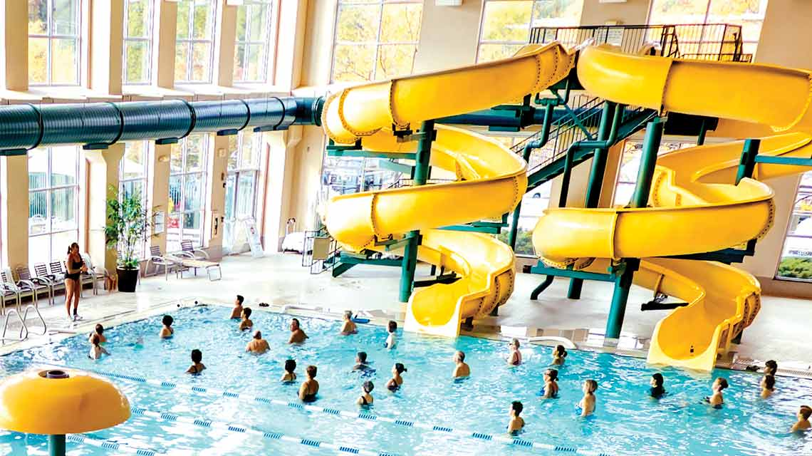 Swimmers playing at the base of two indoor water slides