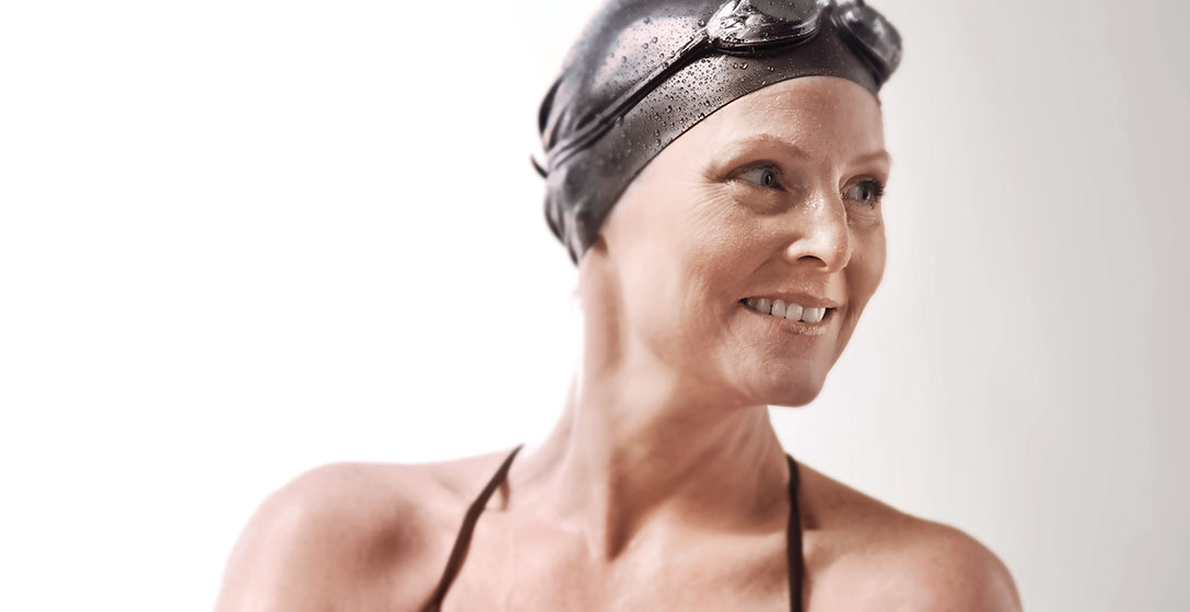 A smiling mature woman in a swim cap and athletic swim suit