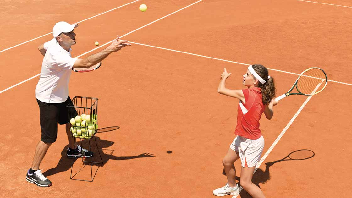 A man tossing a tennis ball to a girl swinging a racquet