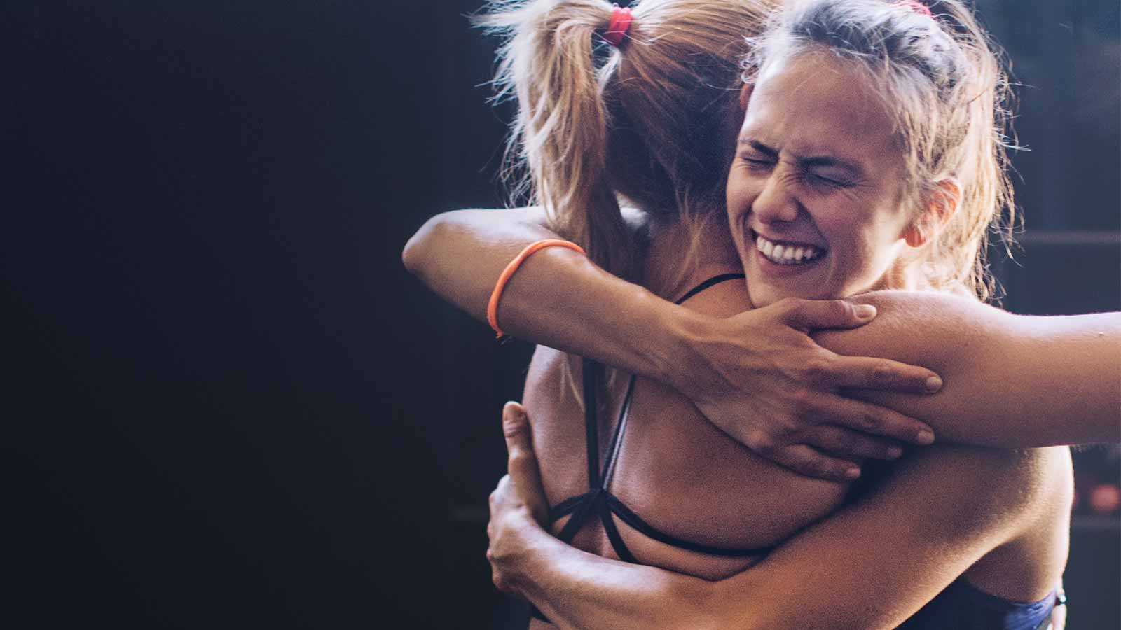 Two happy athletic young women smiling and hugging