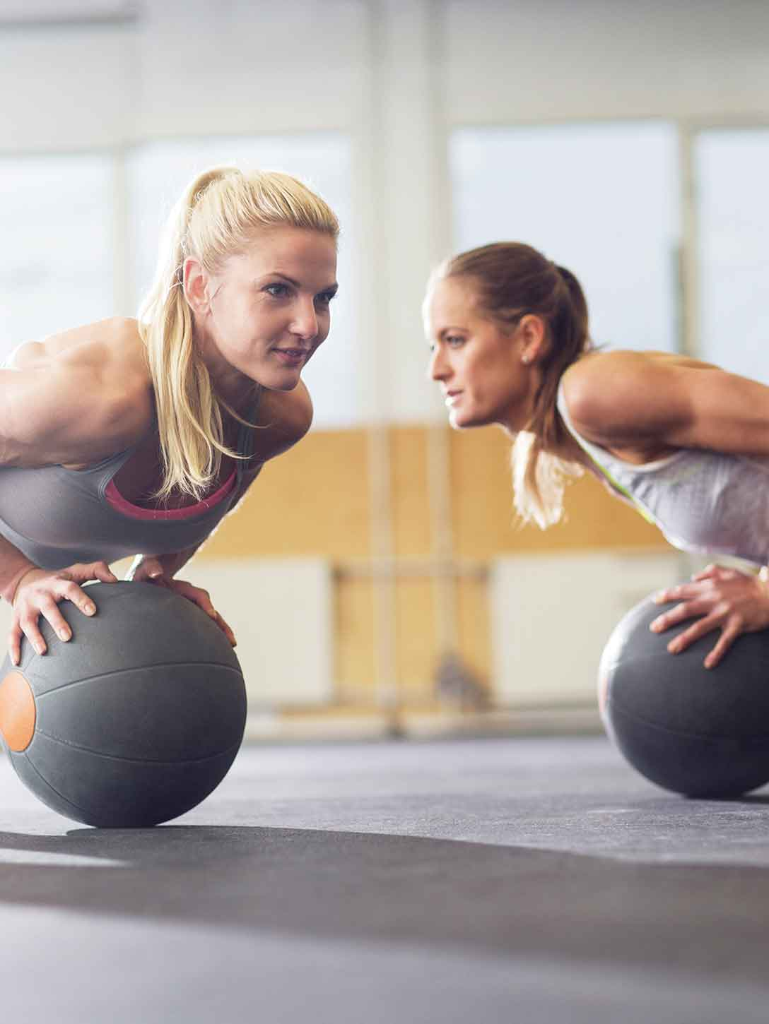 Smiling adults working out on balance balls in a group exercise class