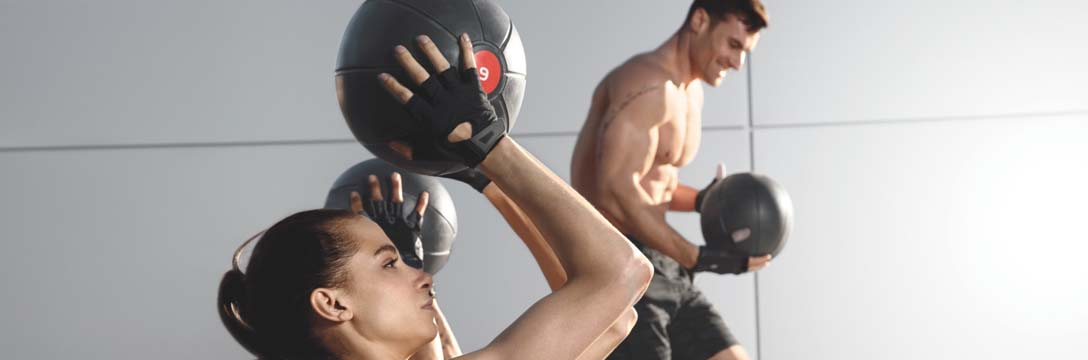 A man and a woman working out with medicine balls.