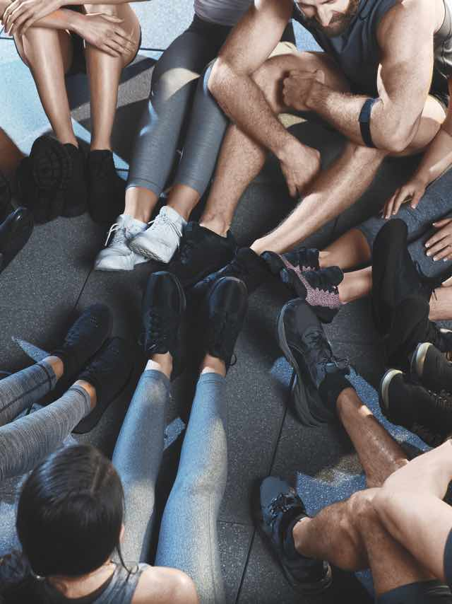 A group of TEAM participants witting in a circle with their feet in the middle