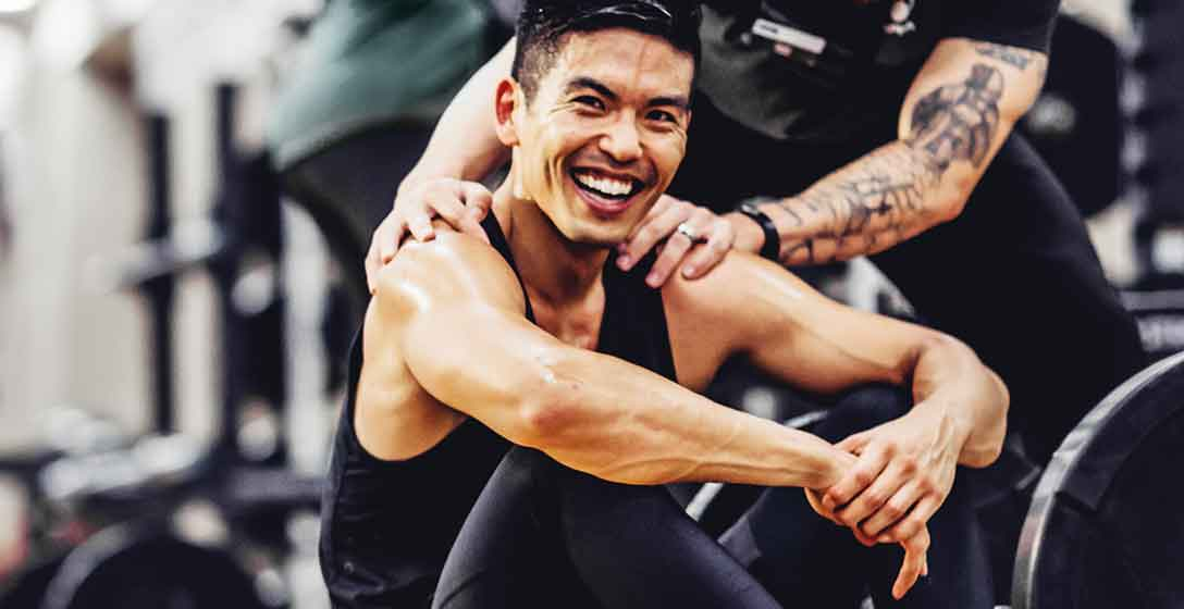 A smiling athletic man taking a break from personal training