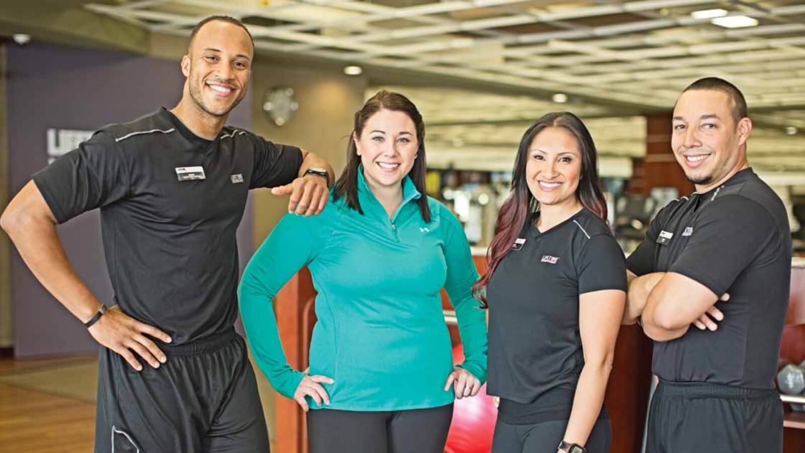 Four Life Time personal trainers stand together smiling