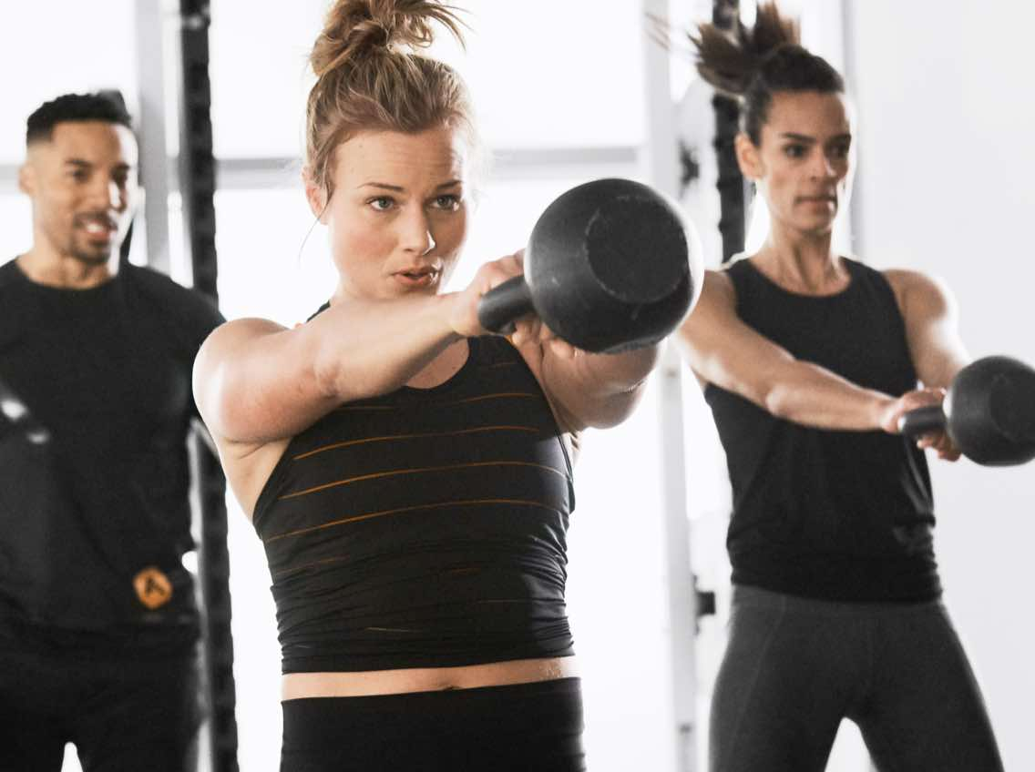 Woman working out with a personal trainer using kettlebells