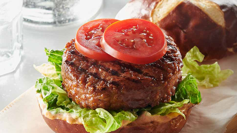 Juicy grass-fed burger on pretzel bun with lettuce and fresh tomato