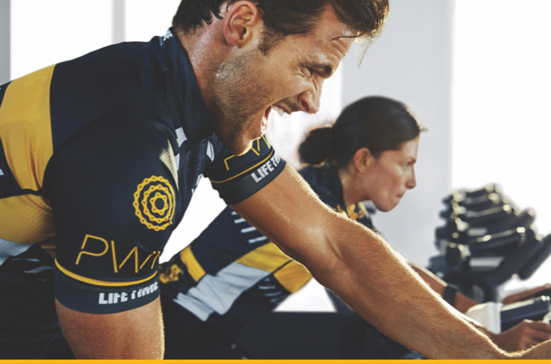 Man and woman riding a bike in Power class