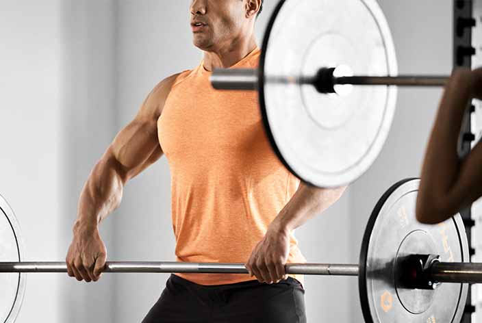 A man in an orange tank top holds a barbell at waist height