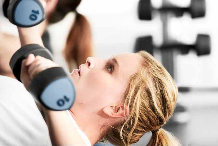 A woman in a white shirt does bench presses with dumbbells
