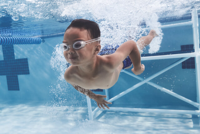 Young boy in swim goggles in a swimming pool