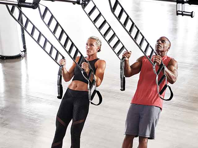 Two Life Time members in workout clothes use suspension ladders to do inverted rows in a club