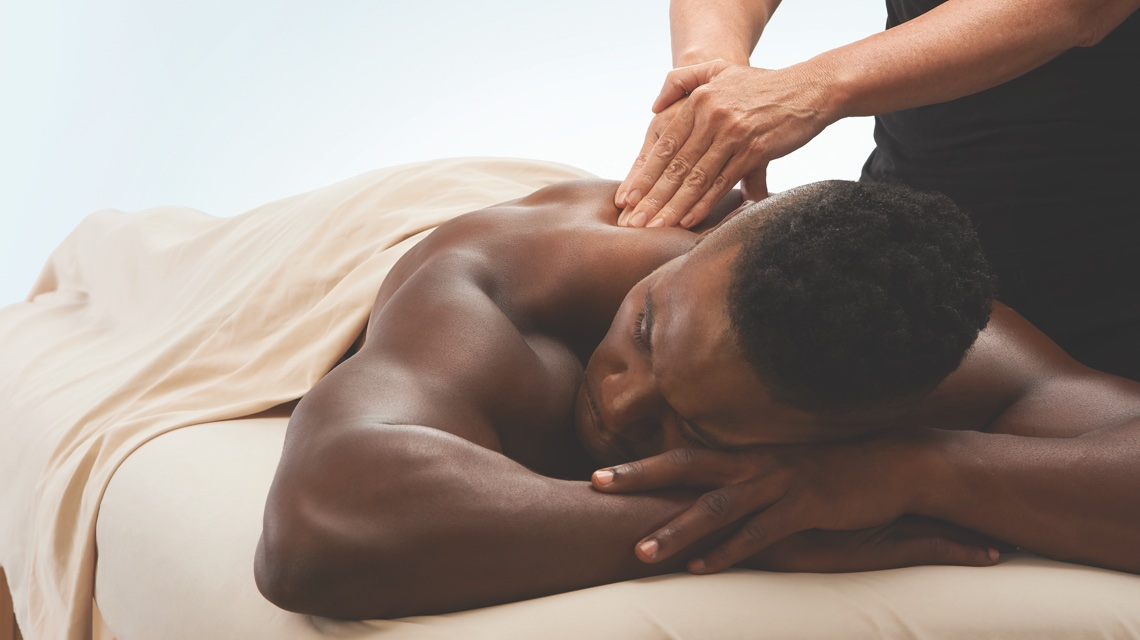 Man lying down on a massage table receiving a shoulder massage