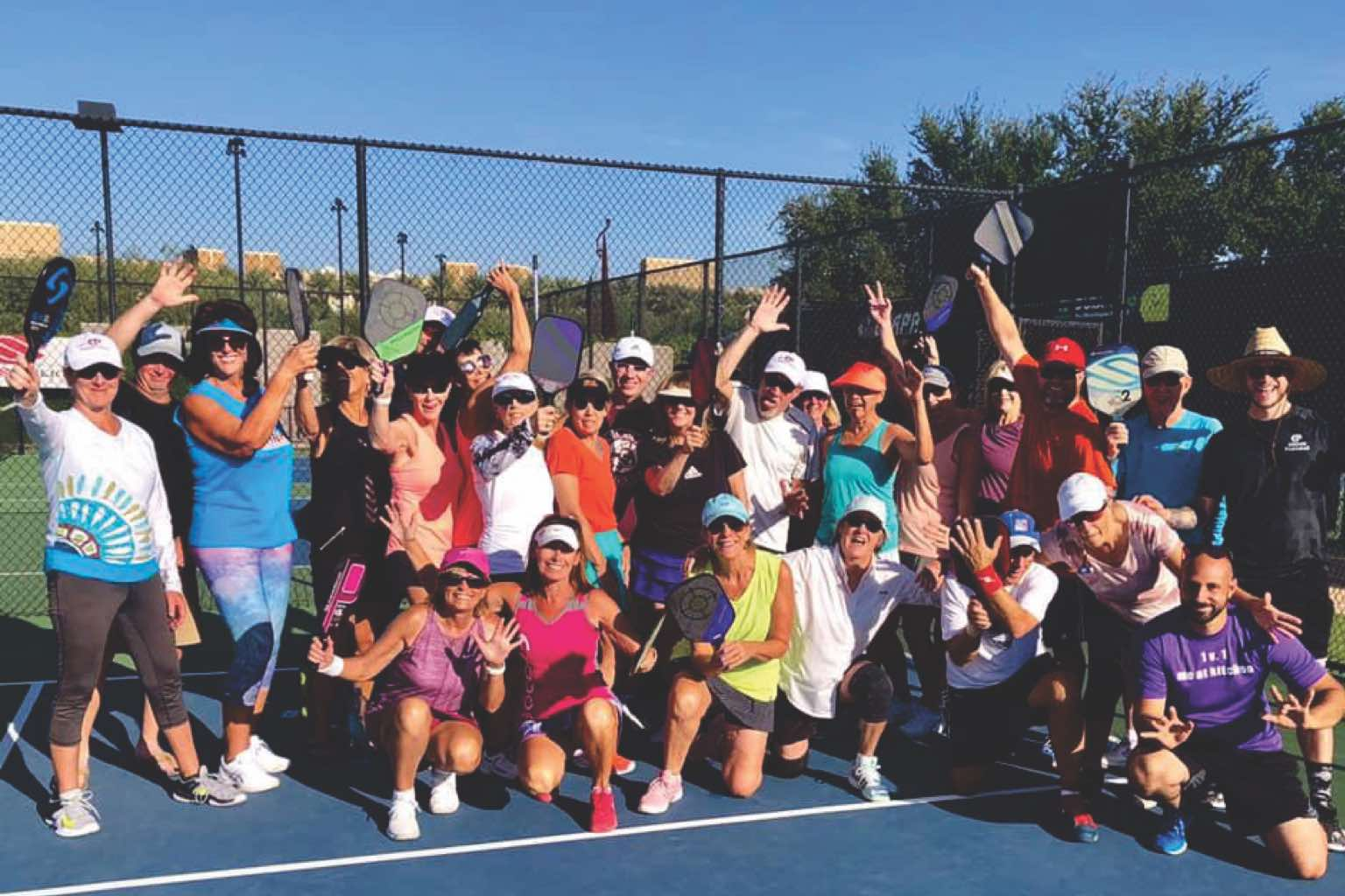 A league of players in a pickleball game at Life Time