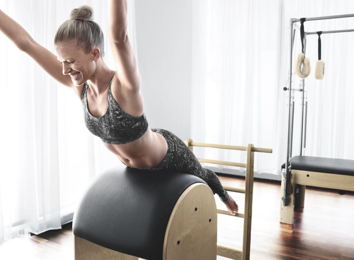 A woman happily performing Pilates moves